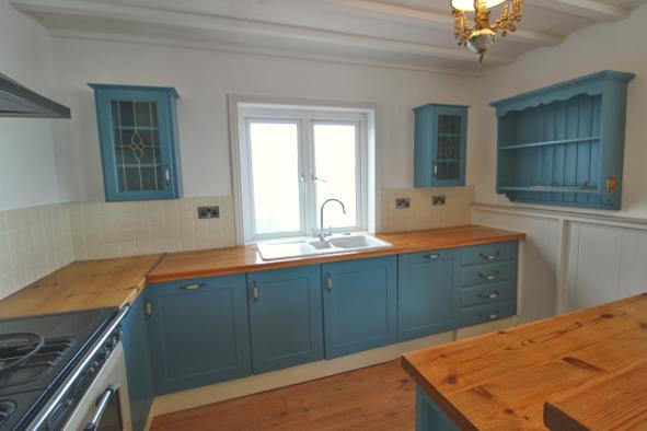 Kitchen cabinets blue painted with brown worktop